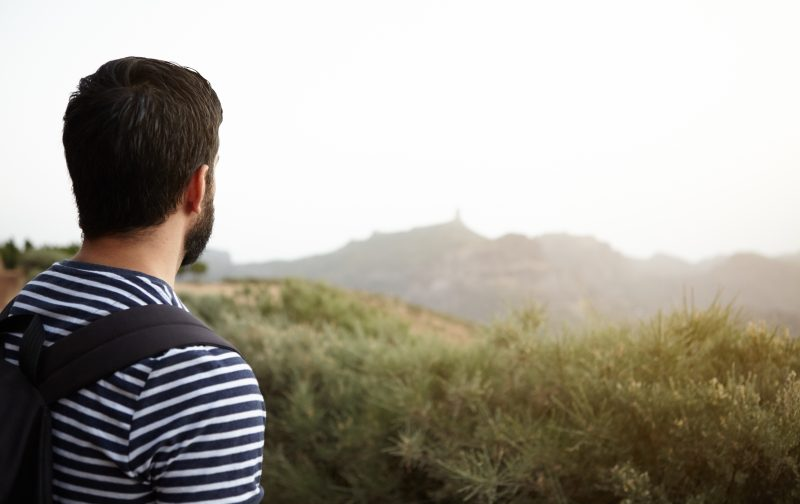 Young man looking out over the mountain in bright sunshine wearing a striped t-shirt with a backpack and a beard